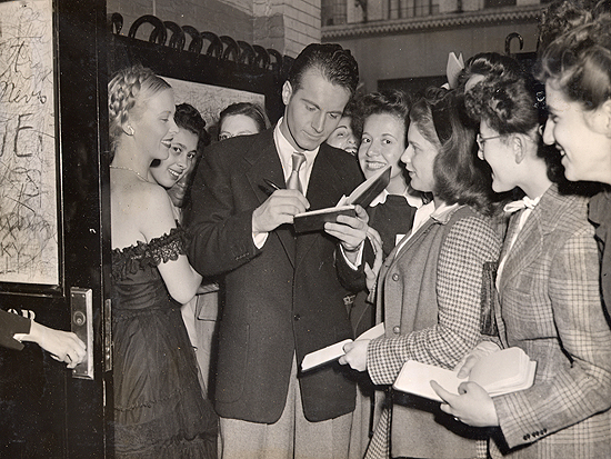 1945 personal appearance tour: Andrea King watches with an amused smile as Helmut Dantine is swarmed by adoring female fans at the stage door.