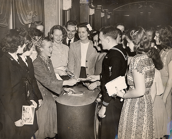1945 personal appearance tour: Andrea King signs autographs in the lobby of the Strand Theatre in Times Square, New York.