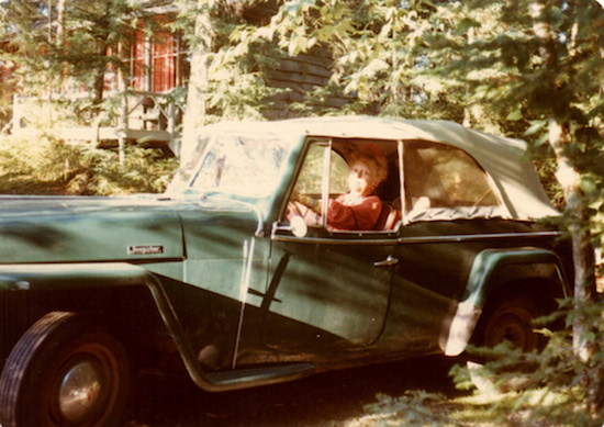 Belle McKee sits proudly behind the wheel of her jeep at her camp in the Adirondacks, part of the original Gardiner-Doing Camp. Late 1970s.