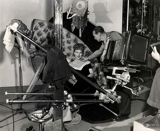 Head photographer, Bert Six, readies Andrea for a pose in the Warner Bros. still gallery. 1945.